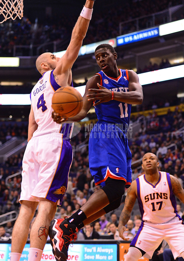 Jan. 2, 2013; Phoenix, AZ, USA: Philadelphia 76ers guard Jrue Holiday (11) passes the ball under pressure from Phoenix Suns center Marcin Gortat (4) in the first half at the US Airways Center. Mandatory Credit: Mark J. Rebilas-USA TODAY Sports