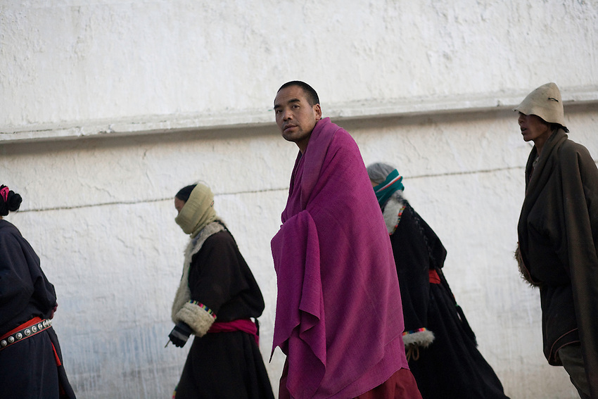 A tibetan monk of the monastery of Labrang is following the pilgrimage path with other Tibetans, in the hope of a better life. Xiahe, China.