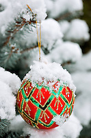 Christmas tree ornament in snow covered tree.