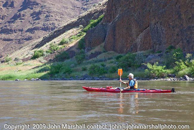 Howie Wallace paddles a kayak past basalt cliffs on the John Day River, Oregon