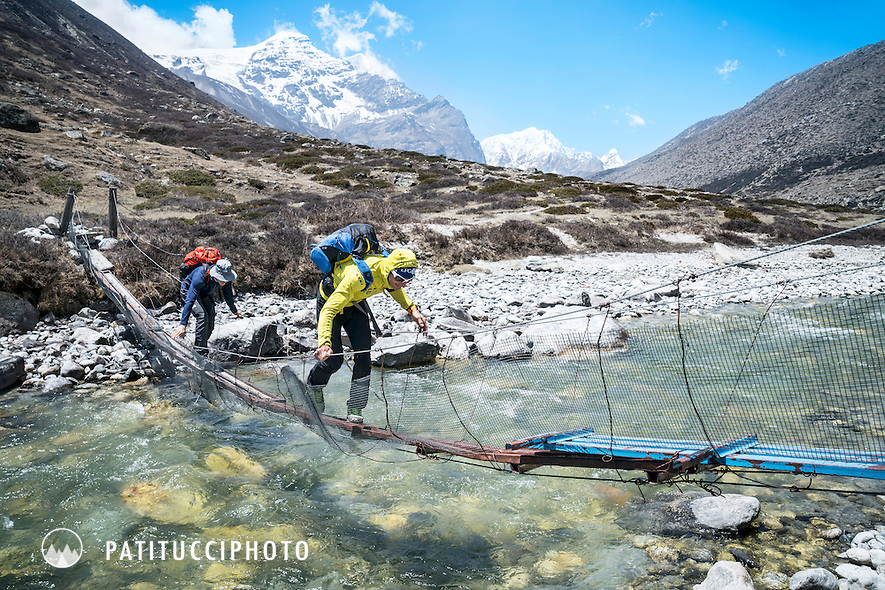 Ueli Steck and David Göttler crossing a suspension bridge during the walk in to Shishapangma, Tibet