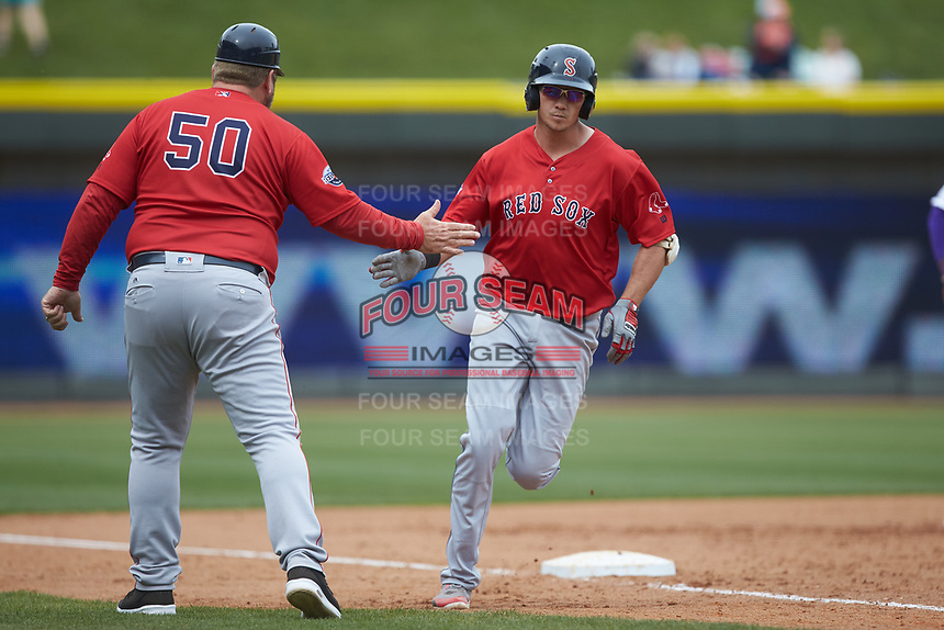 Bobby Dalbec (29) of the Salem Red Sox slaps hands with Salem Red Sox manager Joe Oliver (50) as he rounds third base after hitting a 2-run home run in the top of the 10th inning against the Winston-Salem Dash at BB&T Ballpark on April 22, 2018 in Winston-Salem, North Carolina.  The Red Sox defeated the Dash 6-4 in 10 innings.  (Brian Westerholt/Four Seam Images)
