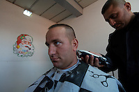 An Italian soldier from the  Fifth  Lancieri of Novara regiment of the Italian Cavalry has his hair cut by a local contracting barber in the UNIFIL Chama base in Southern Lebanon on Friday Dec 08 2006..Close to 1000 Italian peacekeepers operate in  the in Southern lebanon town of Chama, constantly patrolling their sector in search for illegal weapons in the country.