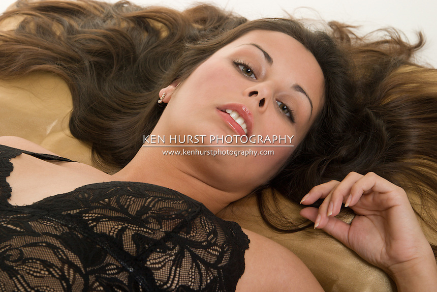 Beautiful Hispanic woman lying down on satin pillow, looking at the one she loves and wants!