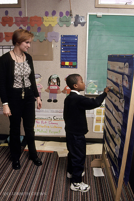 Oakland CA Teacher helping boy seven-years-old identify words on word board in learning handicapped class  MR