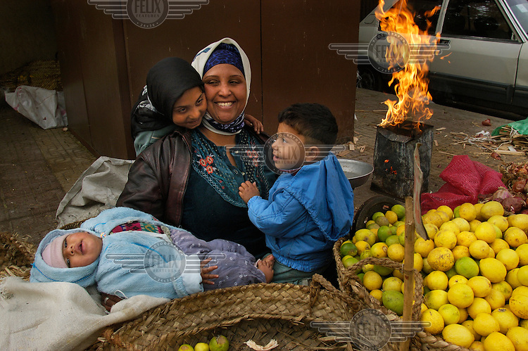 Woman with four children selling vegetables at a street market in the Islamic City, keeping warm in the winter chill with a fire in an old metal can.