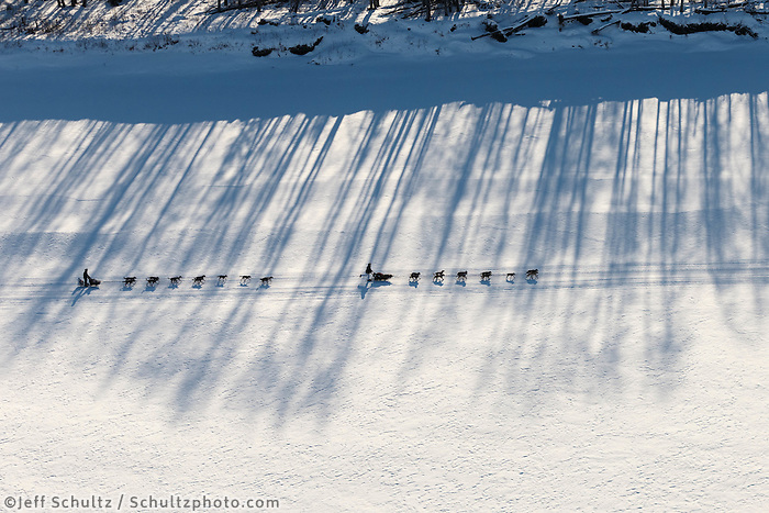 Charlie Bejna and Anna Berington  run in the shadows on the Yukon river between Ruby and Galena on Saturday March 8, during the Iditarod Sled Dog Race 2014.<br /> <br /> PHOTO (c) BY JEFF SCHULTZ/IditarodPhotos.com -- REPRODUCTION PROHIBITED WITHOUT PERMISSION