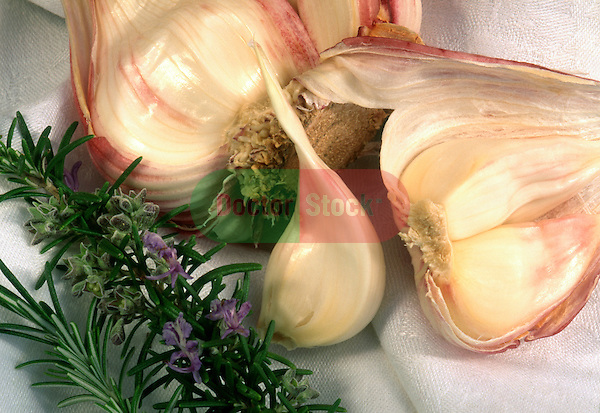 A head of fresh garlic, broken open to reveal the individual cloves, with sprigs of fresh rosemary