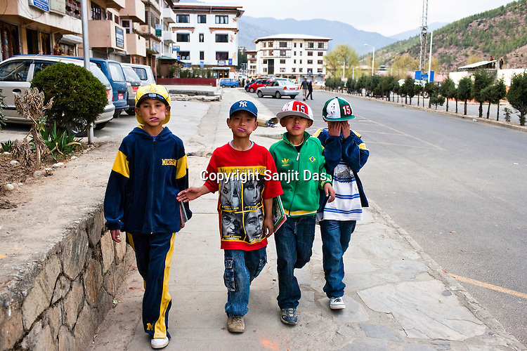 """The traditional Bhutanese outfit, Gho, is mandatory for Bhutanese men, a move made in fear of influence from western culture. But not everyone follows the tradition, like these young kids walking around in hip-hop clothes in the capital Thimpu, Bhutan. Cultural transition in Bhutan is arriving rapidly. Television and the internet have been accessible only since 1999 in Bhutan, and were introduced despite widespread fears that their """"controversial"""" content such as fashion shows, western music, wrestling, and pornography, could destroy the kingdom's traditional way of life based on unique Buddhist principles. Photo: Sanjit Das/Panos"""