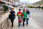 "The traditional Bhutanese outfit, Gho, is mandatory for Bhutanese men, a move made in fear of influence from western culture. But not everyone follows the tradition, like these young kids walking around in hip-hop clothes in the capital Thimpu, Bhutan. Cultural transition in Bhutan is arriving rapidly. Television and the internet have been accessible only since 1999 in Bhutan, and were introduced despite widespread fears that their ""controversial"" content such as fashion shows, western music, wrestling, and pornography, could destroy the kingdom's traditional way of life based on unique Buddhist principles. Photo: Sanjit Das/Panos"