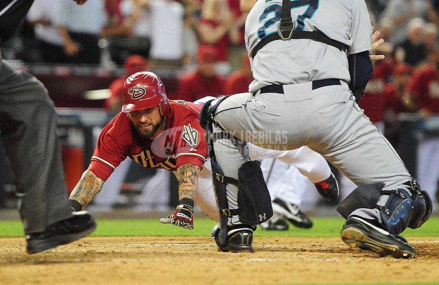 Jun. 20, 2012; Phoenix, AZ, USA; Arizona Diamondbacks third baseman Ryan Roberts dives safely into home to score a two run inside the park home run in the sixth inning against the Seattle Mariners at Chase Field.  Mandatory Credit: Mark J. Rebilas-