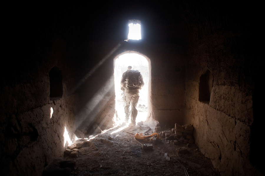 A trooper with Charlie Co. 1st Battalion 12th Infantry Regiment, 4th Infantry Division walks through the doorway of an abandoned home being used by Taliban bomb-makers to produce and store explosives and other IED-making materials in Zhari District, Kandahar, Afghanistan. The violently contested district sits astride the strategically Highway 1 ringroad between Kandahar and Lashkar Gah and is seen by some as the birthplace of the Taliban movement.