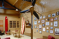 The living room is decorated with surf boards and vintage photographs of surfers