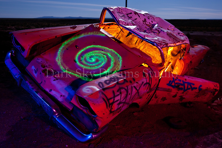 A graffitied, battered and abandoned vehicle  rusts quietly away in the desert night near historic Route 66 and Meteor Crater, outside of Winslow, Arizona