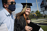 Graduate Audrey Cook reacts after receiving her diploma as she hugs her dad Alex Cook, Friday, July 17, 2020 during a graduation ceremony at Bentonville High School in Bentonville. Check out nwaonline.com/200718Daily/ for today's photo gallery. <br /> (NWA Democrat-Gazette/Charlie Kaijo)