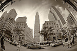 Rockefeller Center, Rockefeller Plaza with GE Building 30 Rockefeller Center emphasized, from under Saks Fifth Avenue's flags, through fisheye lens, with taxis, bus, people passing by, on 5th Ave., Manhattan, NYC, New York, USA, on June 27, 2011. Antique sepia, silvrfx 034 yellow pre-filter, grain added for vintage effect.