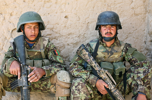 Two Afghan soldiers sit outside a compound while others search inside for a Taliban weapons cache reported to be in the village of Jelewar in the Arghandab valley near Kandahar, Afghanistan. The reported cache was not found. April 4, 2010. DREW BROWN/STARS AND STRIPES