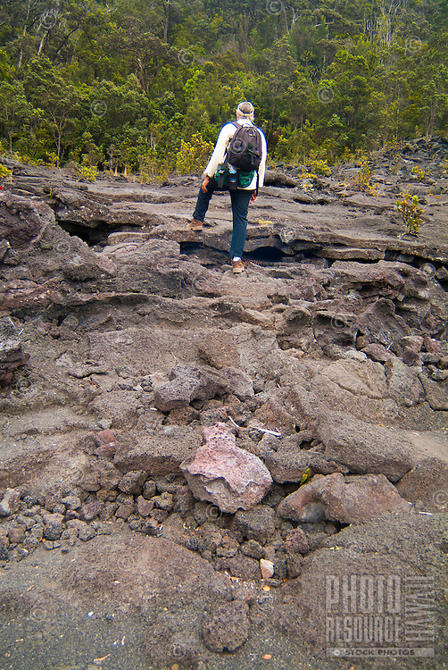 A hiker climbs across broken sheets of hardened lava at the edge of Kilauea Iki Crater (a 1959 lava lake) in Hawai'i Volcanoes National Park, Big Island.