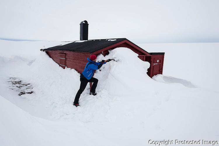 Mann måker fram hytta Helheim på Varangerhalvøya. ---- Man digging out cabin from snow.
