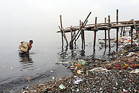 "An Indonesian boy plays with a polystyrene box in the bay of Jakarta. According to the the Climate Reality Project, ""without flood protection measures, sea level rise could expose up to 6 million Indonesians to annual coastal flooding. The worst of the flooding would occur on the island of Java, where Jakarta is located."""