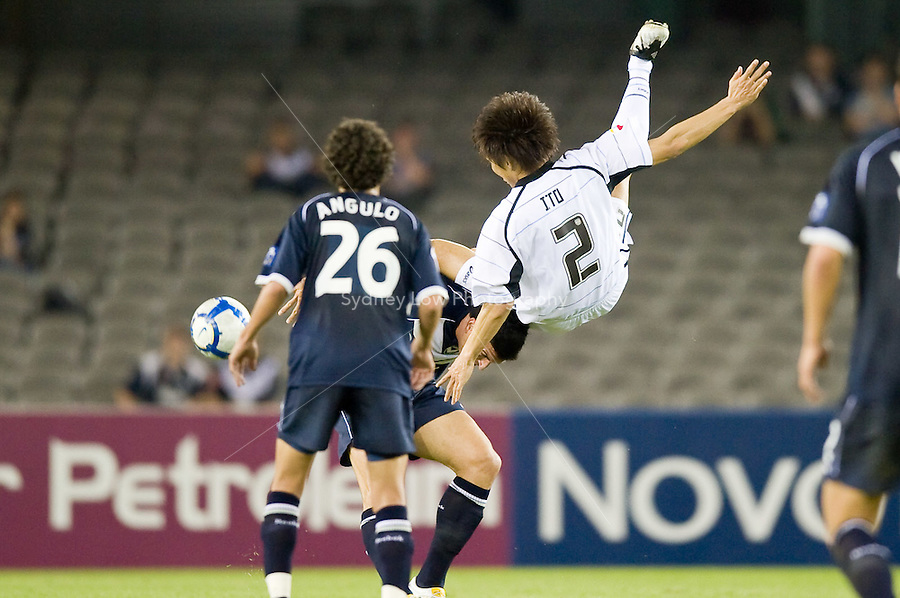 MELBOURNE, AUSTRALIA - MARCH 31, 2010: HIROKI ITO of KAWASAKI FRONTALE jumps on top of Nik Mrdja of Melbourne Victory during the AFC Champions League Group E match between the Melbourne Victory and KAWASAKI FRONTALE at Etihad Stadium on March 31, 2010 in Melbourne, Australia. Photo Sydney Low www.syd-low.com