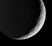In Saturn Orbit - June 27, 2006 -- Rhea's devastated surface creates a jagged terminator as mountains and crater rims break-up the line between day and night. Terrain on Rhea's night side is dimly lit by reflected light from Saturn.  The view looks toward the southern hemisphere on the moon's trailing side. North on Rhea (1,528 kilometers, or 949 miles across) is up.  The image was taken in visible green light with the Cassini spacecraft narrow-angle camera on May 22, 2006 at a distance of approximately 263,000 kilometers (164,000 miles) from Rhea and at a Sun-Rhea-spacecraft, or phase, angle of 138 degrees. Image scale is 2 kilometers (about 1 mile) per pixel..Credit: NASA-JPL-SSI via CNP