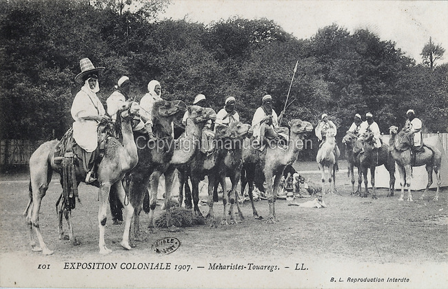 Tuaregs, Berbers from Saharan Africa, riding Mehari dromedaries, at the Colonial Exhibition of 1907, held in the Jardin d'Agronomie Tropicale, or Garden of Tropical Agronomy, in the Bois de Vincennes in the 12th arrondissement of Paris, postcard from the nearby Musee de Nogent sur Marne, France. The garden was first established in 1899 to conduct agronomical experiments on plants of French colonies. In 1907 it was the site of the Colonial Exhibition and many pavilions were built or relocated here. The garden has since become neglected and many structures overgrown, damaged or destroyed, with most of the tropical vegetation disappeared. The site is listed as a historic monument. Picture by Manuel Cohen / Musee de Nogent sur Marne