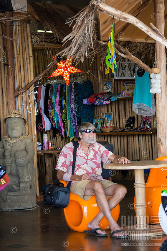 A local senior resident relaxes and listens to  music at the King Kamehameha Market in Hilo, Big Island of Hawai'i.