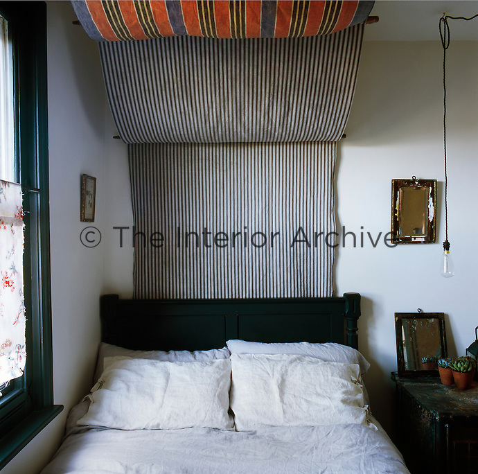 A guest bedroom decorated in a neutral colour palette, with paints from Marston & Langinger and Eico. The bed canopy is made from French ticking and an old beach windbreaker. A metal meat storage container is now a bedside table.
