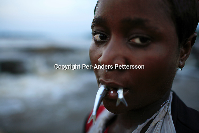 WAGENIA, DEMOCRATIC REPUBLIC OF CONGO MARCH 5: An unidentified young girl keeps her fish in her mouth on March 5, 2006 in Wagenia, a fishing village outside Kisangani, in Congo, DRC. Sh e is fishing in a stream and will later put them in a basket. The village was founded in 1870 and they have been fishing for generations fighting colonialists and nearby tribes. The river is filled with carp, sardines, tilapia, tiger fish and many others. Still young children learn how fish at an early age, and many don?t go to school.  Congo is planning to hold general elections by July 2006, the first democratic elections in forty years..(Photo by Per-Anders Pettersson/Getty Images).
