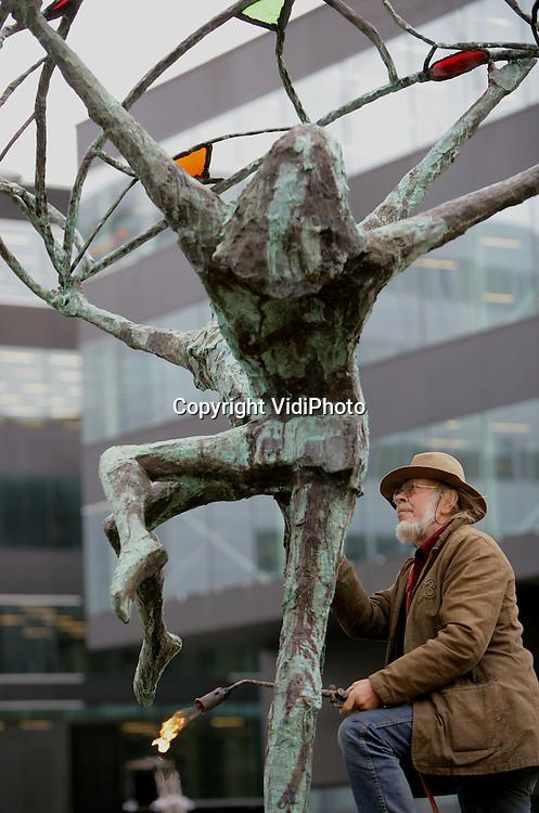 """Foto: VidiPhoto..AMSTERDAM - Schiphol heeft vanaf donderdag een beeld van de internationaal vermaarde kunstenaar Jits Bakker. Het 5 meter hoge bronzen beeld """"Sun in the Wings"""" toont de mens in extase die de wereld wil ontdekken. Het kunstproject heeft zes jaar in beslag genomen, mede veroorzaakt door kritiek van de Kunstcommissie van Schiphol. Voor Bakker als kunstenaar is gekozen omdat zijn beelden op prominente plaatsen over de hele wereld staan. Het kunstwerk, dat donderdag werd geplaatst, wordt maandag officieel onthuld."""