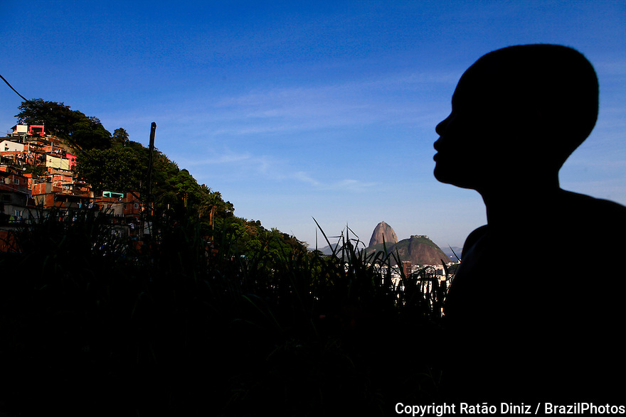 Silhouette of black boy at Favela Santa Marta, Sugar Loaf mountain in background. Since 20o8 the slum has a Pacifying Police Unit ( Unidade de Polícia Pacificadora, also translated as Police Pacification Unit ), abbreviated UPP, a law enforcement and social services program which aims at reclaiming territories, more commonly favelas, controlled by gangs of drug dealers.