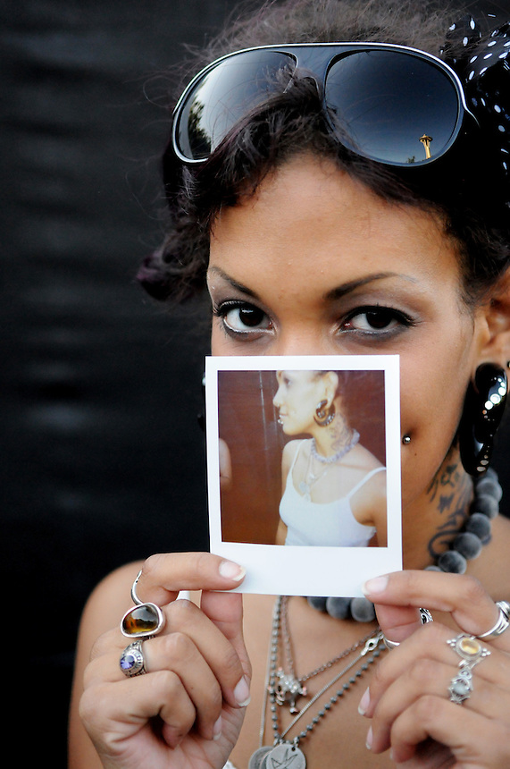 Brianna Franklin of Charlottesville, Virginia holds a Polaroid photo depicting the spiral earrings, necklaces and white tanktop she wore to the 2011 Bumbershoot music and arts festival in Seattle Center on Monday, September 5, 2011.
