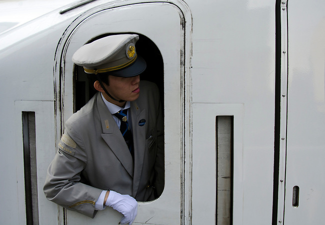 Crew member leans of of windown on the Shinkansen high speed train as it enters Tokyo Station