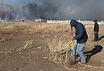 Neighbors put out hot spots as a 400-acre brush fire burns in south Reno, Nev., on Friday, Nov. 18, 2011. More than 25 homes have been lost as high winds with gusts up to 60 mph drive the flames. (AP Photo/Cathleen Allison)