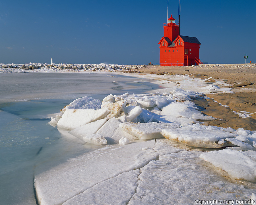 Allegan County, MI  <br /> Red lighthouse at Holland Harbor with ice sheets on the shore of Lake Michigan