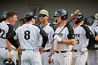 UCF Knights head coach Greg Lovelady (center) talks with Chandler Robertson (22), Ryan Klosterman (8), Dallas Beaver (38), and Tyler Osik (3) during a game against the Siena Saints on February 17, 2019 at John Euliano Park in Orlando, Florida.  UCF defeated Siena 7-1.  (Mike Janes/Four Seam Images)