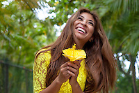 A young local woman holds a yellow hibiscus at Ko Olina Resort, O'ahu.