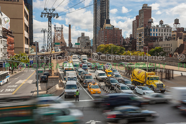 Traffic entering Manhattan from Queens on the Queensboro Bridge waits for crossing traffic on 2nd Avenue in New York City.