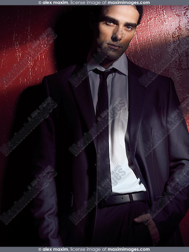 Artistic expressive portrait of a young man in business suit standing against a dark red wall with a stripe of light falling on his face