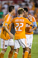 Houston Dynamo midfielders Geoff Cameron (20) and Stuart Holden (22) celebrate a goal with forward Brian Ching (25) advances the ball.  Houston Dynamo defeated D.C. United 4-3 at Robertson Stadium in Houston, TX on August 1, 2009.