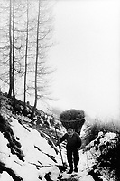 "Switzerland. Canton Graubunden. Viano. Poschiavo valley. Luigi Merlo carries hay on his back in a wood basket, called "" campache"". Winter season. Snow. Manual labor. Labour force.Swiss alpine farmers. Alps mountains peasants.  © 1995 Didier Ruef"