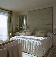 The contemporary bedroom has a large quilted silk panel on the wall above the bed