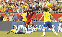 Brazil midfielder Luiz Gustavo (17) slide tackles Portugal forward Nelson Oliveira (9), who goes down. In an international friendly, Brazil (yellow/blue) defeated Portugal (red), 3-1, at Gillette Stadium on September 10, 2013.