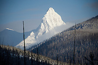 A snow-covered Mount Saint Nicholas stands above the southern edge of Glacier National Park in Montana, USA.  The mountain is part of the Lewis Range.