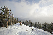 Windy conditions cause snow and clouds to blow across the mountains from the summit of Mount Tecumseh in Waterville Valley, New Hampshire during the winter months.