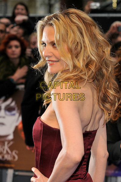 Michelle Pfeiffer.'Dark Shadows' european premiere, Leicester Square, London, England..9th May 2012.half length red maroon burgundy strapless dress hand on hip profile looking over shoulder .CAP/PL.©Phil Loftus/Capital Pictures.