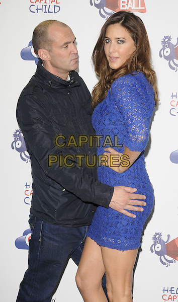JOHNNY VAUGHAN & LISA SNOWDON.The Capital FM Summertime Ball, Wembley Stadium, London, England..June 12th, 2011.half length black jacket jeans denim blue crochet dress hand on hip side profile touching grabbing funny .CAP/CAN.©Can Nguyen/Capital Pictures.
