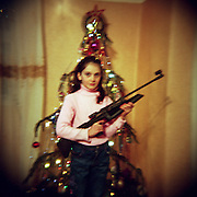 The girl poses with a pneumatic gun standing by the  Christmas tree. Abkhazia.  Gudauta town. 2011