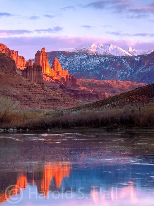 The well known Fisher Towers about 20 miles outside of Maob reflect in the Colorado River as the setting sun makes them glow a brilliant red.